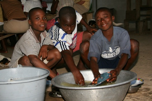 The children wash their own dishes after meals.